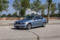 全景BMW 320D蓝色 都市的场面 库存照片