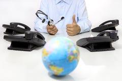 全球性国际支持概念、耳机和办公室在有地球地图的书桌上打电话 免版税库存照片