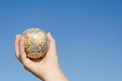全球性地球在手中在蓝天背景,亚洲 免版税库存图片