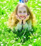 全盛时期概念 微笑的面孔的女孩花费休闲户外 说谎在草的女孩在grassplot,绿色背景 孩子 库存图片