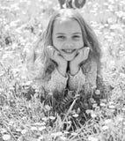 全盛时期概念 微笑的面孔的女孩花费休闲户外 说谎在草的女孩在grassplot,绿色背景 孩子 免版税库存照片