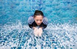 全身泳装的妇女在蓝色水池 库存照片