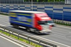 全速移动在六条车道高速公路的大物品车 免版税图库摄影