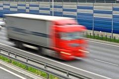全速移动在六条车道高速公路的大物品车 免版税库存图片