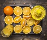 全部与榨汁器和一杯的桔子在木盘子木土气背景顶视图关闭的汁液 库存照片