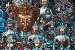 全部古铜和银肩并肩雕刻菩萨金黄颜色的各种各样的大小,立场,紧紧互相,蓝色微光 免版税库存图片