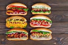 全部大可口热狗用调味汁和菜在木背景 免版税库存照片