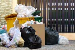 全部废物箱回收,并且垃圾塑料袋在篱芭家,许多破坏废塑料袋前面房子,污染垃圾 库存照片