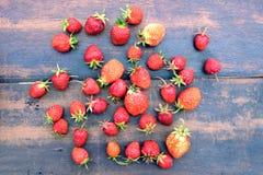 全部成熟开胃草莓在老葡萄酒木背景顶视图特写镜头驱散了 免版税库存图片