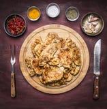 全部油煎的开胃鸡牛排用草本辣椒和大蒜与一把叉子刀子在一个圆的切板在土气w 库存照片