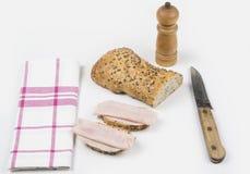 全部的做面包的粮谷 两个切片用火腿和刀子 图库摄影