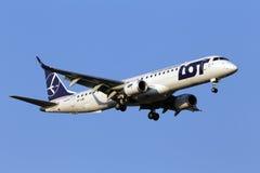 全部-在蓝天背景的波兰航空公司巴西航空工业公司ERJ-195航空器 免版税库存照片