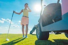 全长一名活跃妇女谈话在高尔夫球场的手机 免版税库存图片