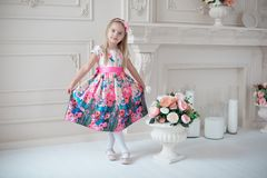 全长五颜六色礼服摆在的小微笑的女孩孩子室内 免版税库存照片
