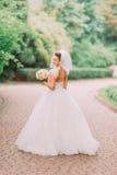 全长后面观点的有拿着婚礼花束的光秃的肩膀的新娘在公园的背景 库存图片