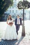 全长室外结婚照 有红色和桃红色花花束的美丽的深色的新娘站立 免版税库存图片