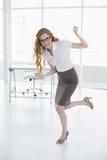 全长快乐的典雅的女实业家在办公室 免版税库存照片