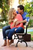 全长愉快的夫妇在日期一起坐长凳笑 库存照片