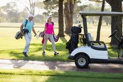 全长成熟高尔夫球运动员夫妇乘高尔夫球儿童车 免版税库存照片