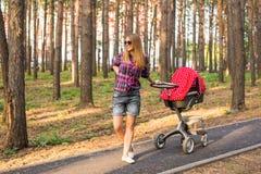 全长有一辆婴儿推车的年轻母亲在公园 库存图片