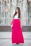 全长有站立在喷泉前面的长的红色裙子的年轻白种人女性室外 图库摄影