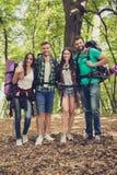 全长木头的四个快乐的朋友在早期的秋天 T 免版税库存照片