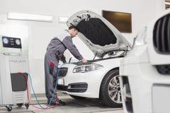 全长男性在汽车维修车间的工程师审查的汽车 免版税库存照片