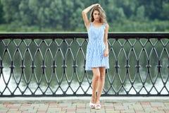 全长白色蓝色的画象年轻美丽的妇女镶边了礼服,夏天rver公园户外 免版税库存图片