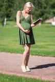 全长的孕妇与书 库存照片