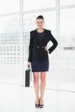 全长衣服运载的公文包的一名典雅的女实业家在办公室 免版税图库摄影