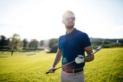 全长观点的拿着高尔夫俱乐部和击中bal的盖帽的人 免版税库存图片