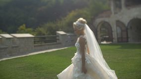 全长观点的跑沿庭院的长的时髦的婚礼礼服的Th可爱的白肤金发的新娘在日落期间 影视素材