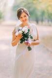 全长画象轻的白色褂子的一个美丽的肉欲的年轻新娘和摆在拿着婚礼花束的公园 库存图片
