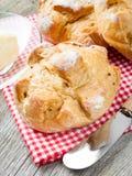 全麦的法国小圆面包和黄油在厨房用桌上 免版税库存图片