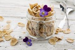 全麦谷物、莓果和可食的花一顿健康早餐的概念在一朵庭院紫罗兰在光 库存图片