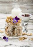 全麦谷物、莓果和可食的花一顿健康早餐的概念在一朵庭院紫罗兰在光 库存照片