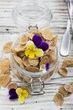 全麦谷物、莓果和可食的花一顿健康早餐的概念在一朵庭院紫罗兰在光 免版税库存图片