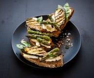 全麦面包三明治用希腊白软干酪,烤夏南瓜,绿色芦笋,糖豌豆,在一个黑色的盘子的橄榄油 免版税库存图片