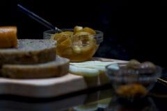 全麦面包用乳酪、果酱和绿橄榄在一块木砧板有他们的反射的,关闭,宏观 库存照片