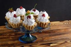 八个蛋糕用蛋白质在玻璃立场的奶油和夏天莓果在木桌上 库存图片