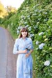 八仙花属从事园艺 年轻美丽的妇女画象长的蓝色礼服的在圣地的米格尔,亚速尔群岛不可思议的开花的公园 库存照片