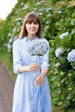 八仙花属从事园艺 年轻美丽的妇女画象长的蓝色礼服的在圣地的米格尔,亚速尔群岛不可思议的开花的公园 免版税库存图片