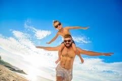 八岁男孩坐爸爸` s担负 两个在游泳短裤和太阳镜,获得在海滩的乐趣 底视图 免版税库存图片