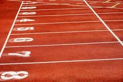 八条赛跑者轨道在体育体育场内 免版税库存照片
