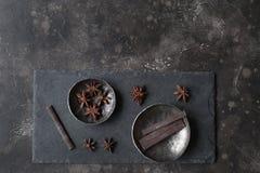 八角和黑暗的巧克力在银器在葡萄酒染黑ta 免版税库存照片