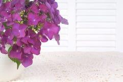 八仙花属在白色桌布的一个花瓶开花与白色背景区、室或者空间拷贝、文本,或者您的词的。 免版税库存照片