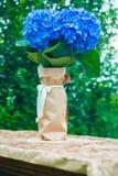 八仙花属花束在桌上的在多雨的庭院里 免版税库存照片