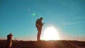 公人和狗相当它价值旅游与背包智能手机航海阳光站立在山顶部 慢的行动 股票录像