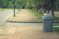 公众在公园回收站或被分离的废物箱有绿色自然本底 免版税库存图片