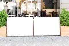 公众,户外咖啡馆的大信息委员会的空白的海报嘲笑在城市 免版税库存照片